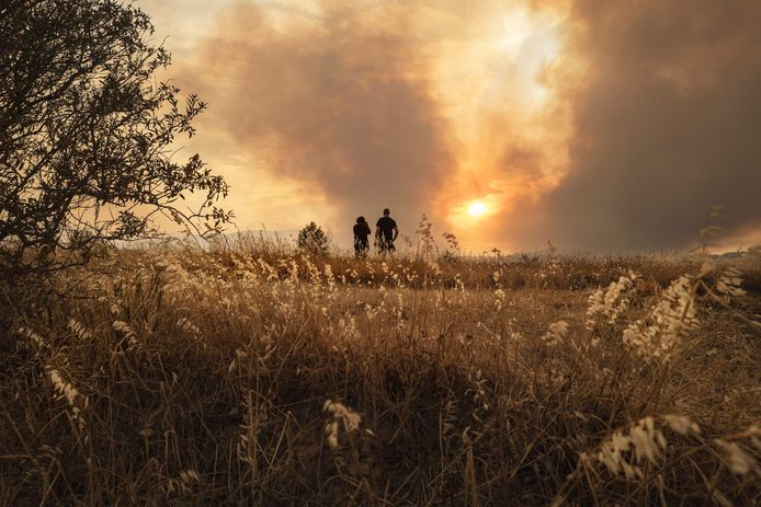 Locals watch a forest fire in southern France from a distance.