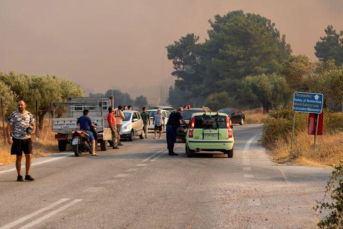 Tourists and residents watch a massive fire near Kalamonas on the Greek island of Rhodes.