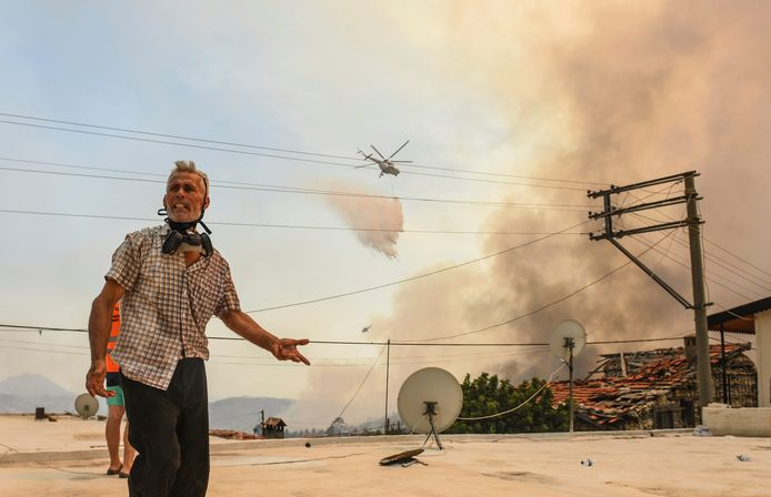 A resident of Sirtkoy village, near Manavgat in Antalya Province, a firefighting helicopter appears in the background.