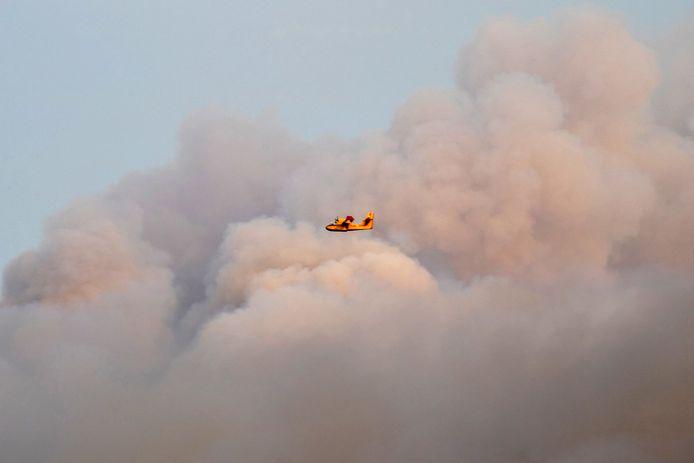 A firefighting plane works to put out a massive fire near Kalamonas.