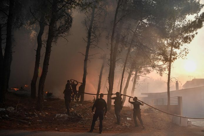 Police officers help firefighters put out a fire in Thracomakdones.